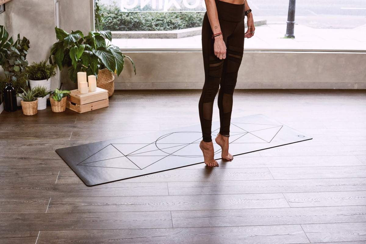woman tip toeing on yoga mat